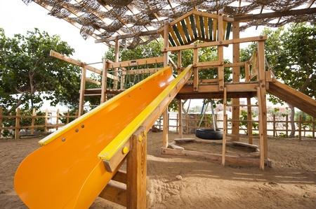 climbing frame: Childrens struttura in legno di arrampicata con scivolo in un parco giochi al parco