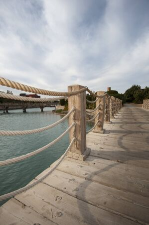 handrails: Wooden bridge with rope handrails over water at a tropical resort with an overcast sky background