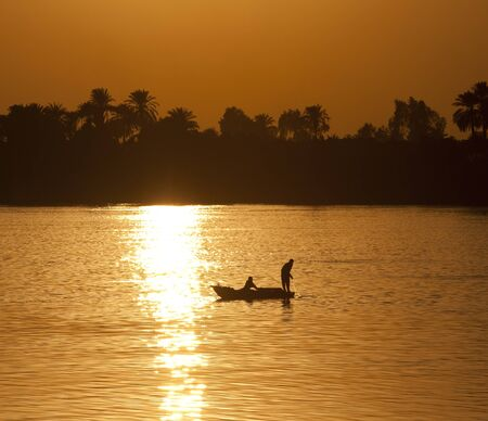 Traditional egyptian fishermen in a rowing boat on the Nile at sunset photo