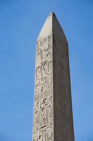 obelisk stone: Large ancient obelisk with egyptian hieroglyphics at Karnak temple in Luxor against a blue sky background Stock Photo