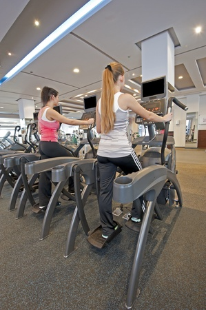 Two young women on step machines at a gym photo