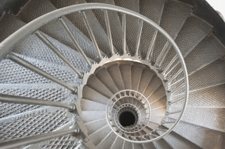 View down a spiral staircase in a lighthouse seemingly going to infinity photo