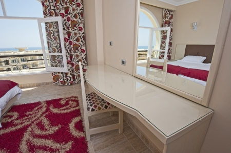 Luxury hotel bedroom dressing table and mirror with a tropical sea view photo