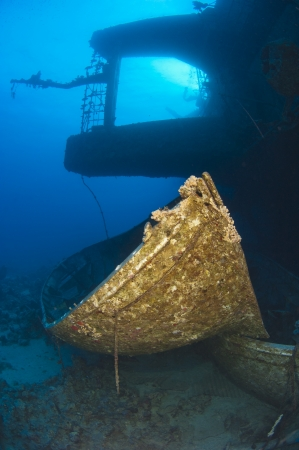 Ships lifeboat on the seabed with silhouette of a shipwreck in the background photo