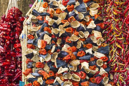 bunches: Bunches of dried vegetables hanging at an outdoor market stall Stock Photo