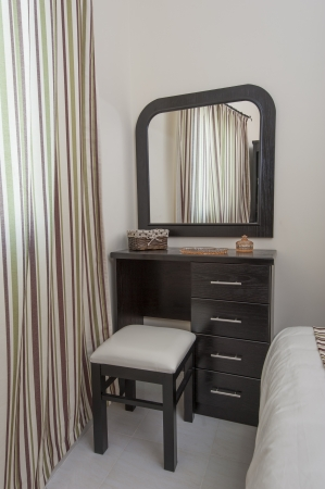 Dressing table with stool and mirror in a bedroom