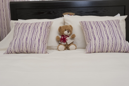 Teddy bear and pillows on a bed in a bedroom of apartment photo