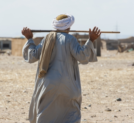 rural town: Traditional egyptian bedouin walking through a remote rural town Stock Photo
