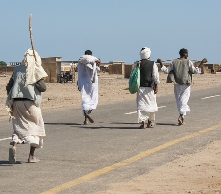 rural town: Four traditional egyptian bedouins walking down a road in a remote rural town
