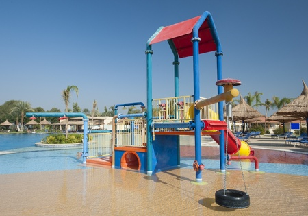 Climbing frame and slide in children's play area of a shallow swimming pool