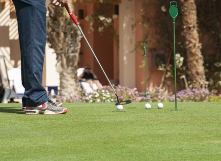Male golfer on a practice putting green photo