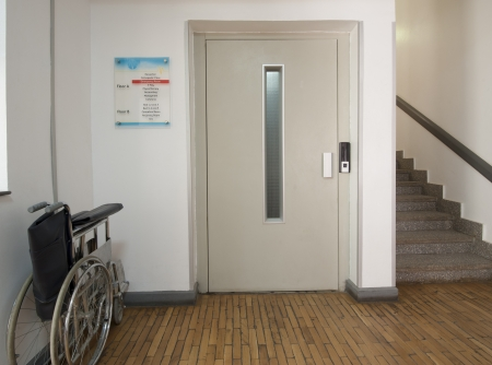 Entrance foyer in a medical centre with elevator and wheelchair photo
