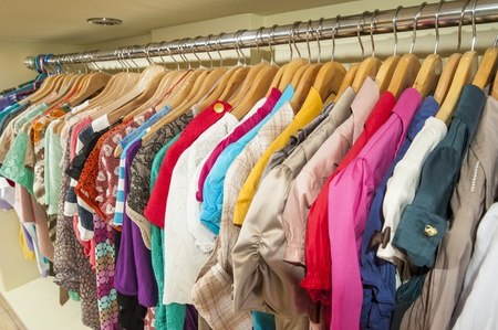 clothes rail: Various multi-colored items of clothing hanging on hangers and rail in a shop