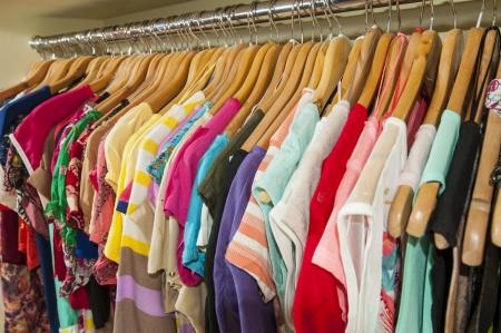 ropa colgada: Varios artículos de varios colores de ropa colgada en perchas y ferroviarios en una tienda