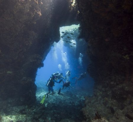Scuba divers exploring an underwater sea cave in a tropical coral reef Stock Photo - 21357773