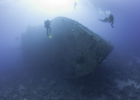 Scuba divers exploring a large sunken underwater shipwreck photo