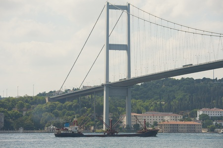 Large cargo ship traveling under a suspension bridge on bosphorus river in istanbul turkey Stock Photo - 21967816