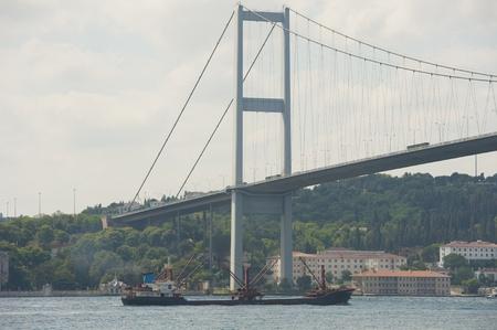 Large cargo ship traveling under a suspension bridge on bosphorus river in istanbul turkey Stock Photo - 21967816