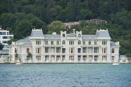 Large luxury villa on the water front with wooded hillside in background Stock Photo - 21844484