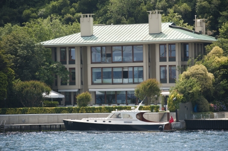 Large luxury villa on the water front with private motor yacht Stock Photo - 21969625