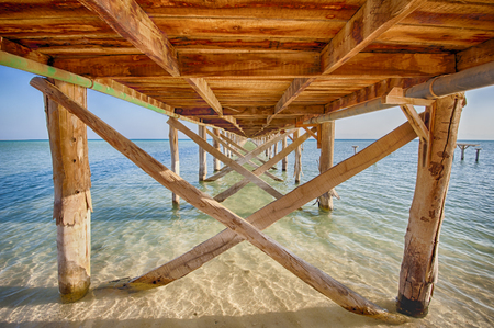 underneath: HDR image of a wooden jetty stretching out to sea from tropical desert island
