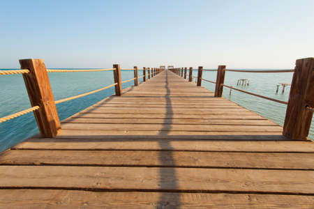 Long wooden jetty on a tropical island stretching out into the sea