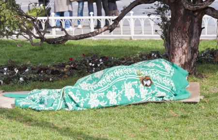 Lone homeless person asleep under an old blanket outside in a city center park
