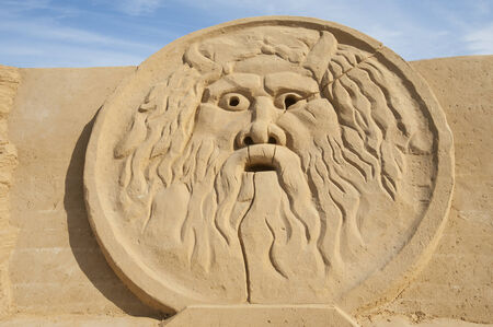 greek god: Large sand sculpture of greek god zeus in relief Stock Photo