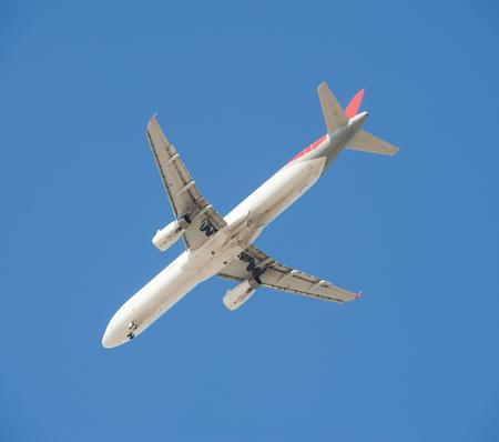 underbelly: Aerei passeggeri di grandi dimensioni in volo con carrello gi� come si viene a terra isolato su uno sfondo blu cielo Archivio Fotografico