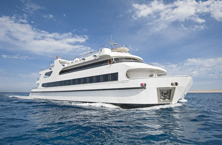 starboard: Large steel luxury private catamaran motor yacht sailing out at sea Stock Photo