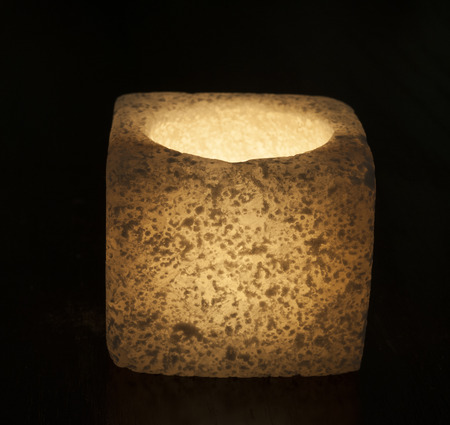 tealight: Ornate rock salt tealight candle holder isolated on a black background