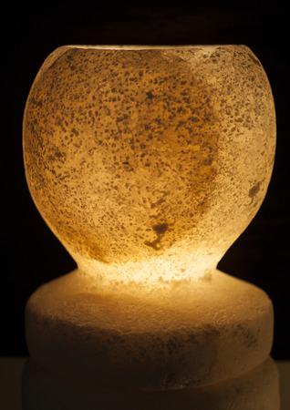 salt lamp: Ornate rock salt lamp and holder isolated on a black background