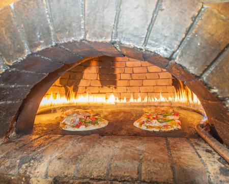 Pizzas para cocinar en el interior de un horno de pizza tradicional con llamas Foto de archivo