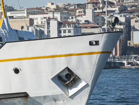 ship bow: Bow of a large metal ship in port against cityscape  Stock Photo