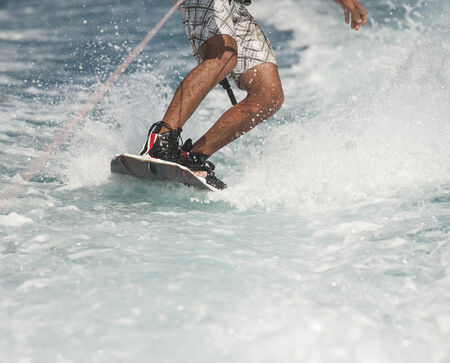 board shorts: Closeup detail of wakeboarder on water behind speedboat Stock Photo