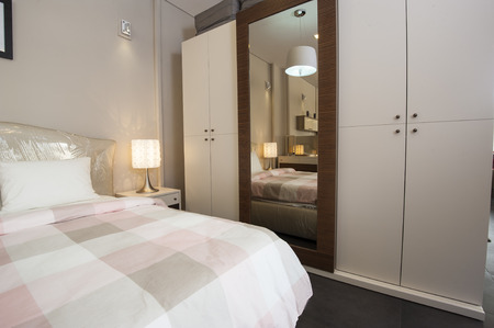 Bedroom area in show home with wardrobe and lamps Banco de Imagens