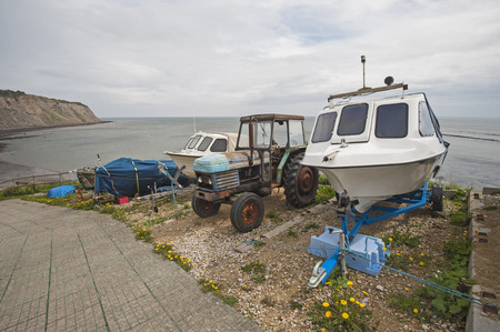 slipway: Small pleasure boat and old tractor on english coastal slipway by the sea