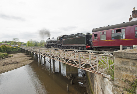 Traditional steam train in english rural countryside travelling on bridge over river with overcast sky photo