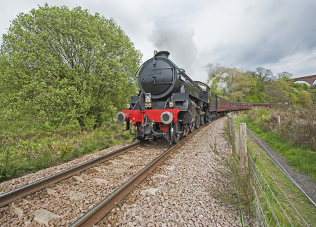 Old english steam train travelling along tracks through rural countryside scenery photo