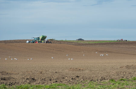 Tractor seeding rural agricultural arable fields in english countryside