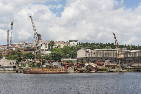 drydock: Old abandoned derelict dockyards by large river in city Stock Photo