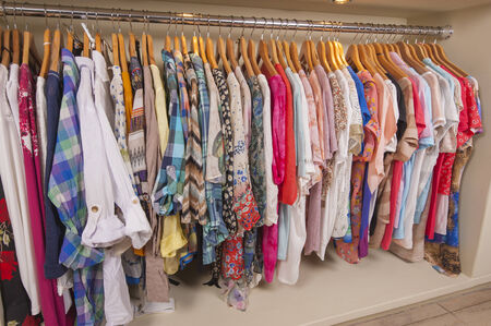 womens clothing: Variety of colorful womens clothing hanging on rail in fashion shop