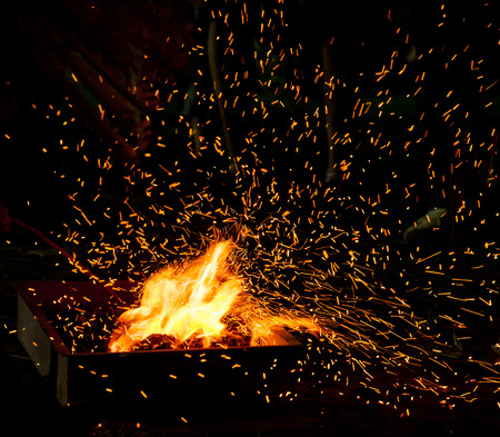 fire flame: Small BBQ on fire with burning charcoal and flying sparks