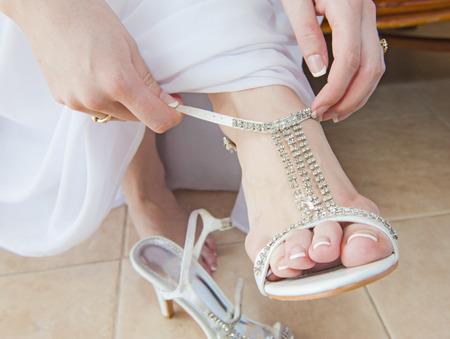 heel strap: Closeup detail of bride putting on high heeled sandal wedding shoes