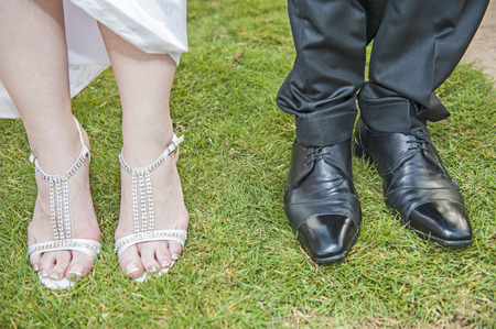 heel strap: Closeup of bride and grooms feet with shoes standing together on grass
