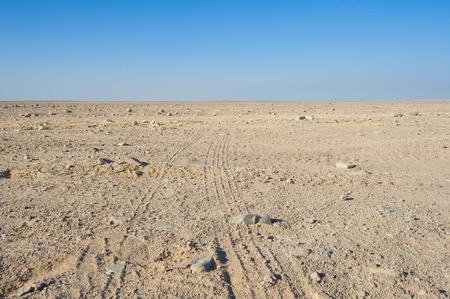 Vehicle tyre tracks going through a desolate arid rocky desert landscape Stock Photo