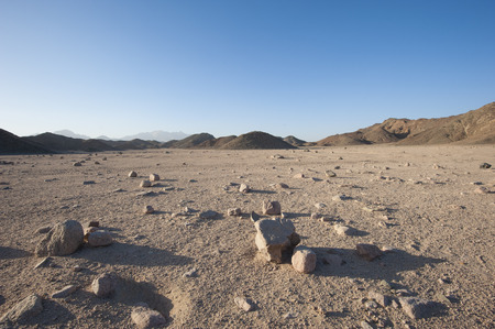Closeup detail of stony desolate arid desert landscape with mountains 写真素材