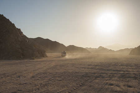 off road vehicle: Off road vehicle on safari traveling through arid desolate desert landscape with sunset Stock Photo
