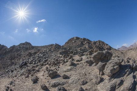 Peak of rocky mountain in arid desert landscape against blue sky background with sun