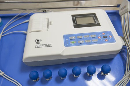 ecg monitoring: Closeup detail of an ECG machine with electrodes in a medical center hospital Stock Photo